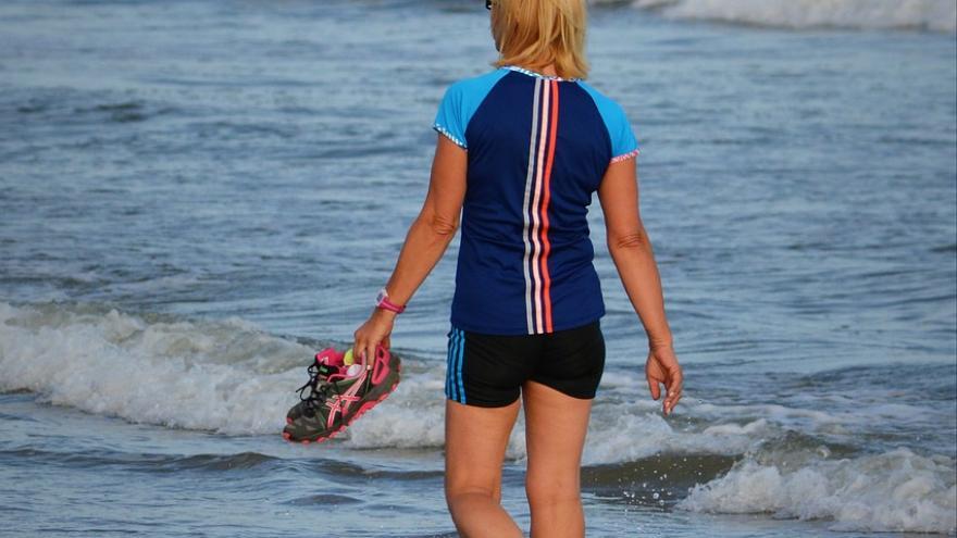 mujer caminado por la playa