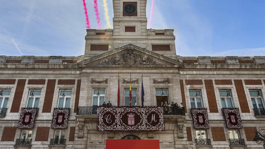 Siete cazas sobrevolando la Real Casa de Correos soltando humo con los colores de la Comunidad de Madrid