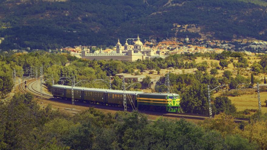 Tren de Felipe II viajando por la vía con San Lorenzo de El Escorial al fondo
