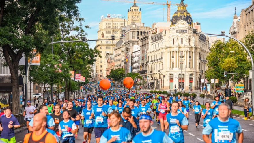 La Gran Vía con muchas personas corriendo con camiseta azul, imagen corporativa de la carrera
