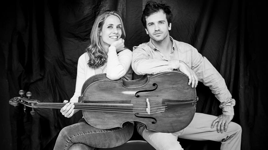 Componentes del grupo un hombre y una mujer sostienen un violonchelo juntos