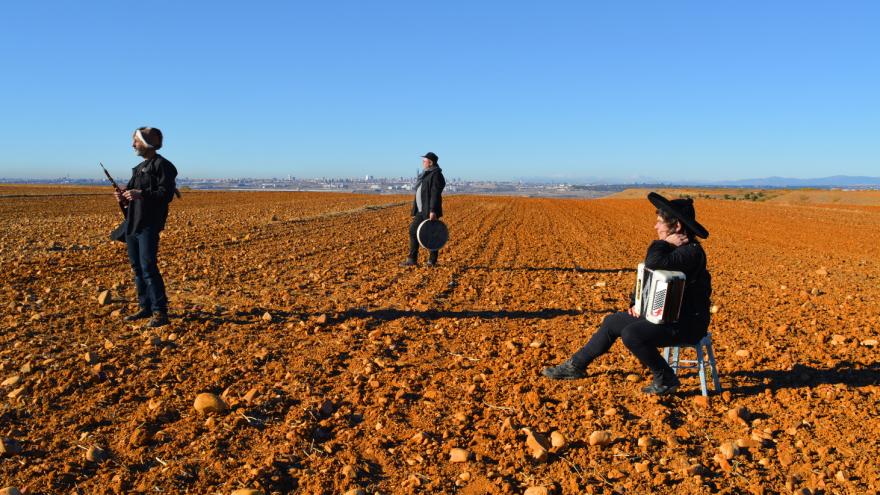 Fotografía de tres personas en una explanada de arena marrón