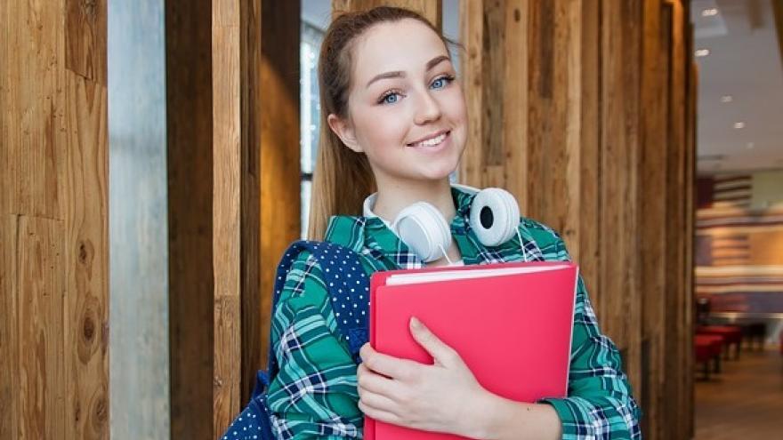 Chica con carpeta en la mano y cascos colgados