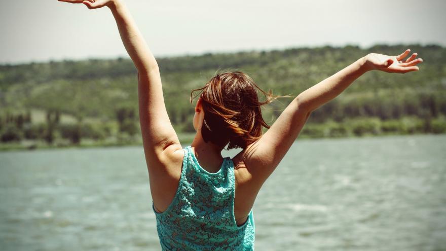 Chica de espaldas levantando los brazos