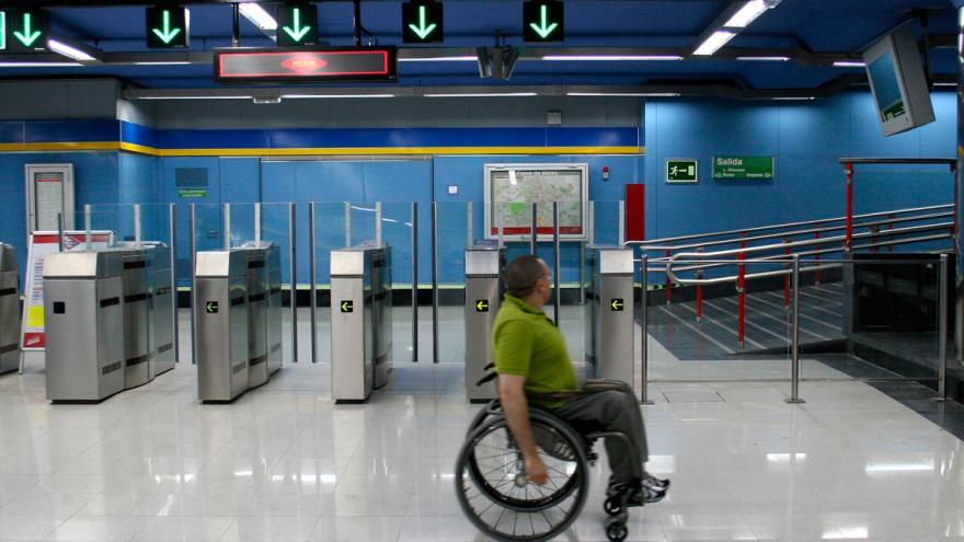 Persona en silla de ruedas en un vestíbulo de Metro