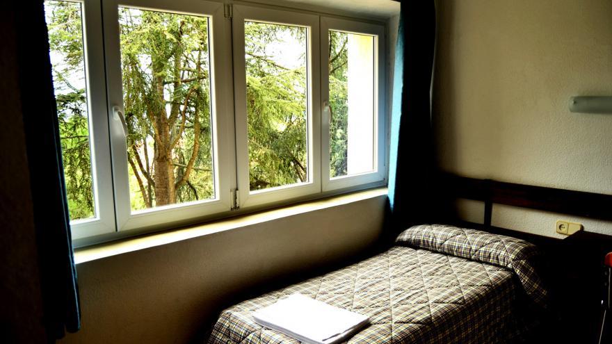 Habitación con cama y ventana albergue El Escorial