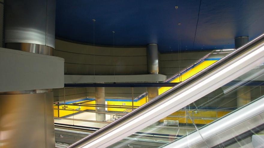 Estación Hospital de Móstoles. Vista desde las escaleras mecánicas, techo azul intenso, vitrex de la estación amarillo y columnas de acero
