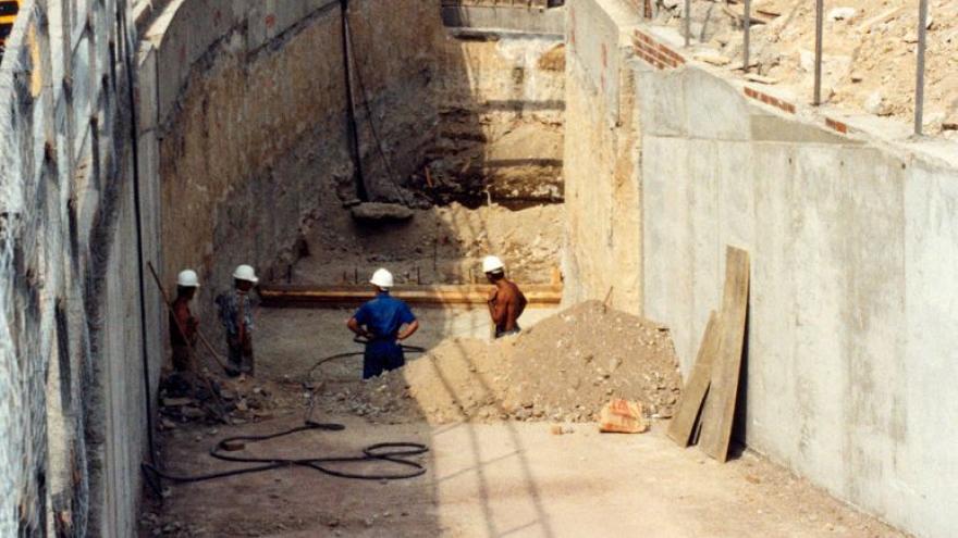 Rampa de acceso, alrededor maquinaria, obreros, camiones