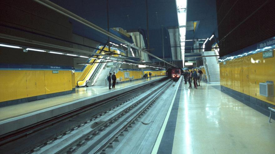 Tren entrando en la estación Villa de Vallecas, personas esperando en los andenes