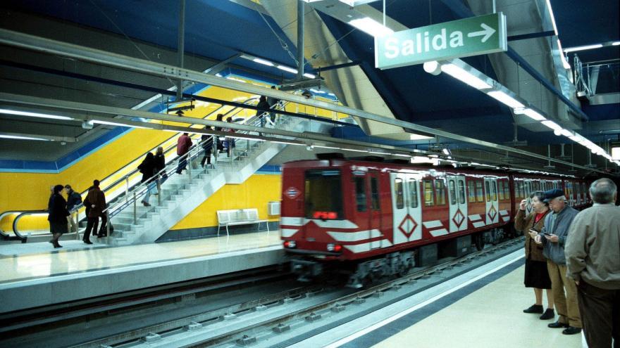 Tren saliendo de la estación Villa de Vallecas, personas utilizando las escaleras