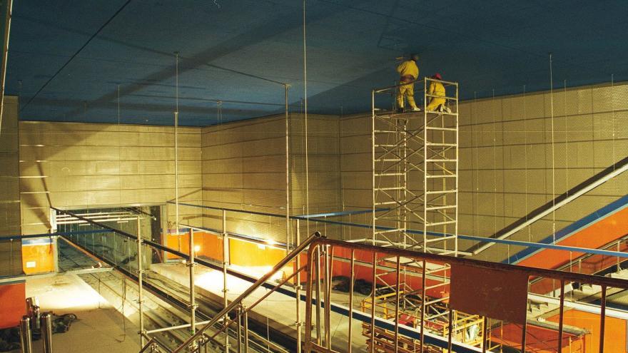 Obreros subidos a un andamio pintando el techo de azul de la estación Congosto