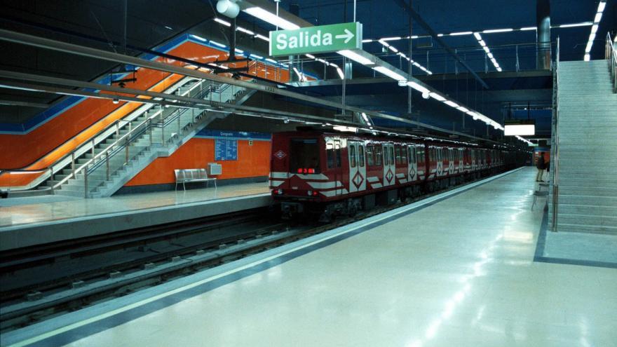 ndenes y cuerpo de escaleras de la estación Congosto con tren saliendo de la estación