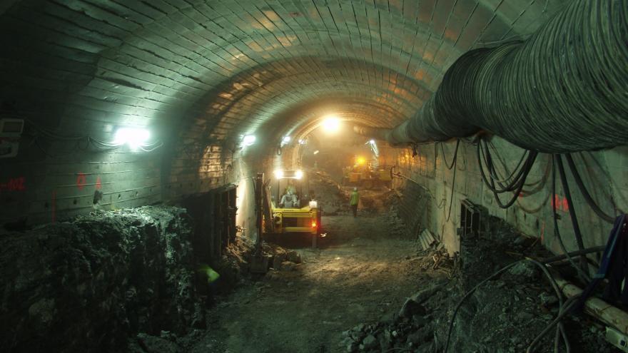 Túnel iluminado en obras con maquinaria y obreros trabajando