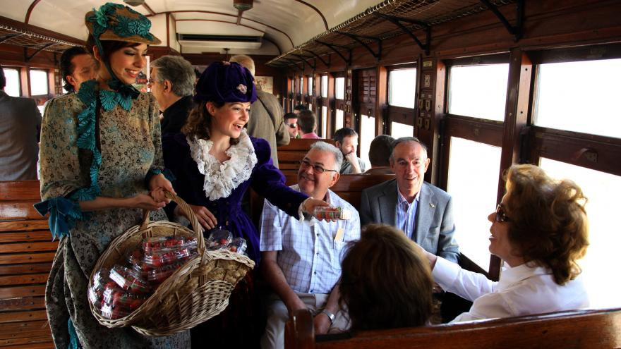 Pasajeros del Tren de la Fresa reciben una caja de fresas de dos mujeres vestidas de época
