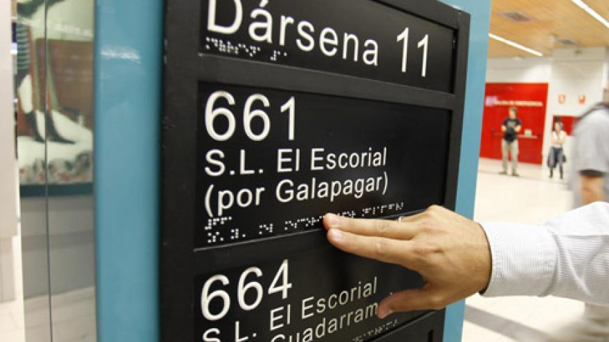 Mano sobre texto en braille en el intercambiador de Moncloa