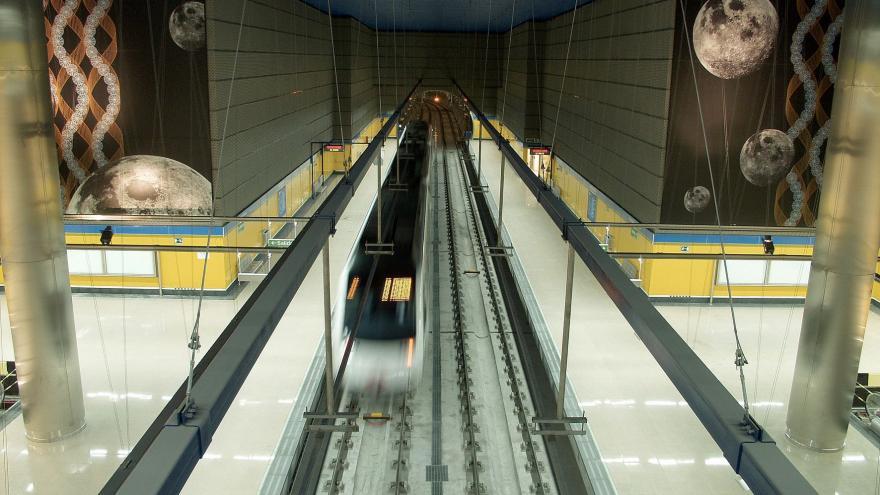 Vista de la estación con el tren en la misma, los murales en los laterales