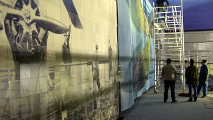Personal subidos a un andamio colocando el mural