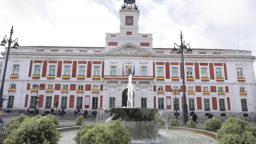 Fachada de la Real Casa de Correos decorada con la bandera española