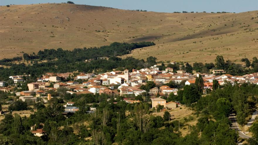 Vista panorámica de Canencia de la Sierra en un valle con colinas al fondo