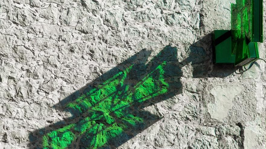 Cruz verde reflejado en pared