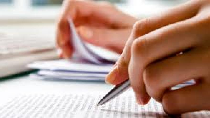 Mano con bolígrafo escribiendo en un folio