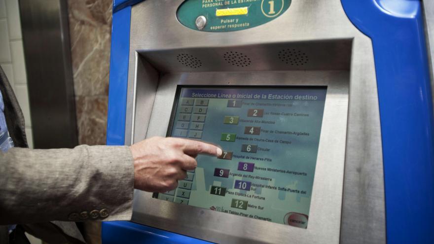 Mano seleccionando un billete en una máquina expendedora de Metro