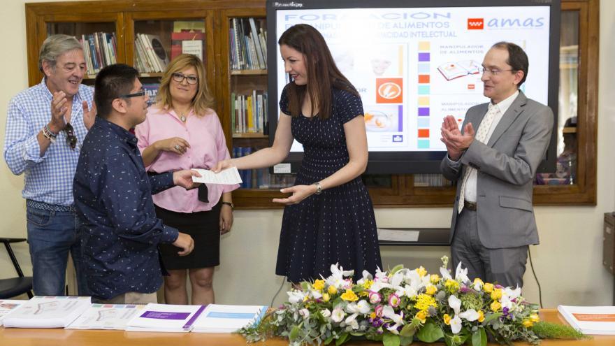 La consejera de Política Social en funciones, Lola Moreno, entregando uno de los diplomas