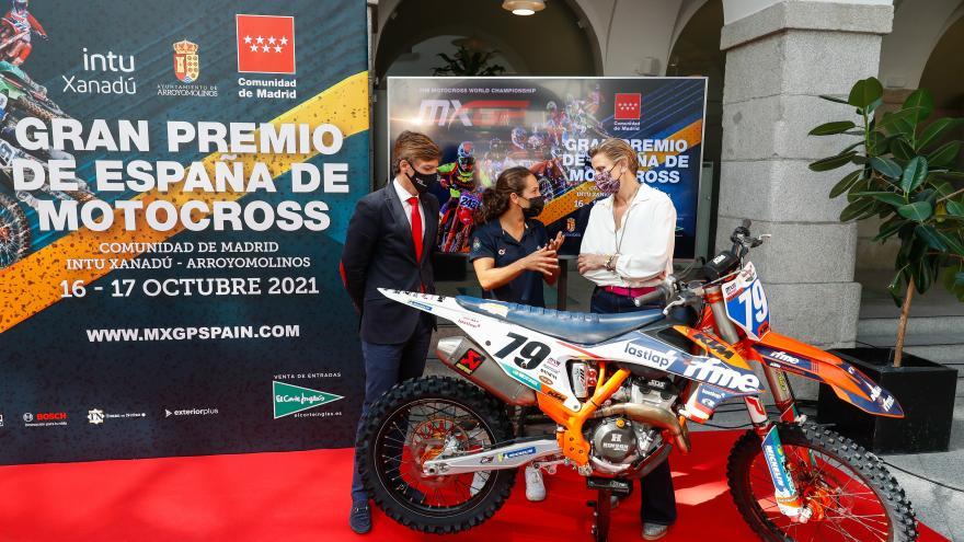 El viceconsejero junto con la directora general detrás de una motocicleta hablando con una de las participantes del Gran Premio