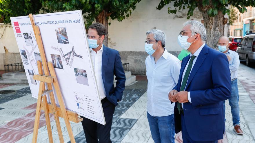 El consejero junto al alcalde y otro asistente mirando un cartel informativo sobre la actuación que se va a realizar en el municipio