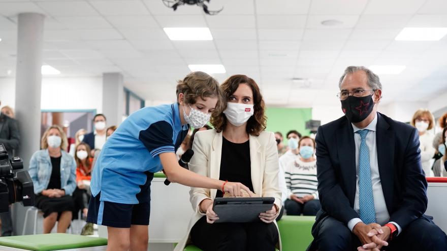 La presidenta mirando en una tablet donde una niña le señala algo