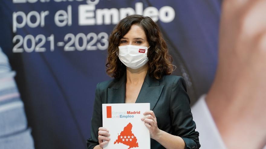 """La presidenta sujetando un libro donde se lee """"Estrategia Madrid por el Empleo 2021-2023"""""""
