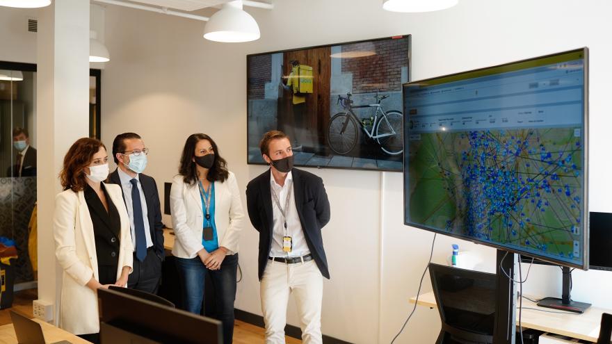 La presidenta junto a los responsables de Glovo mirando una pantalla con un mapa