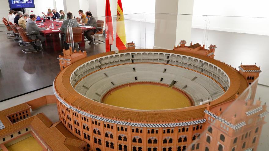 Primer plano de la maqueta de la Plaza de las Ventas y de fondo la mesa de la reunión con todos los participantes sentados