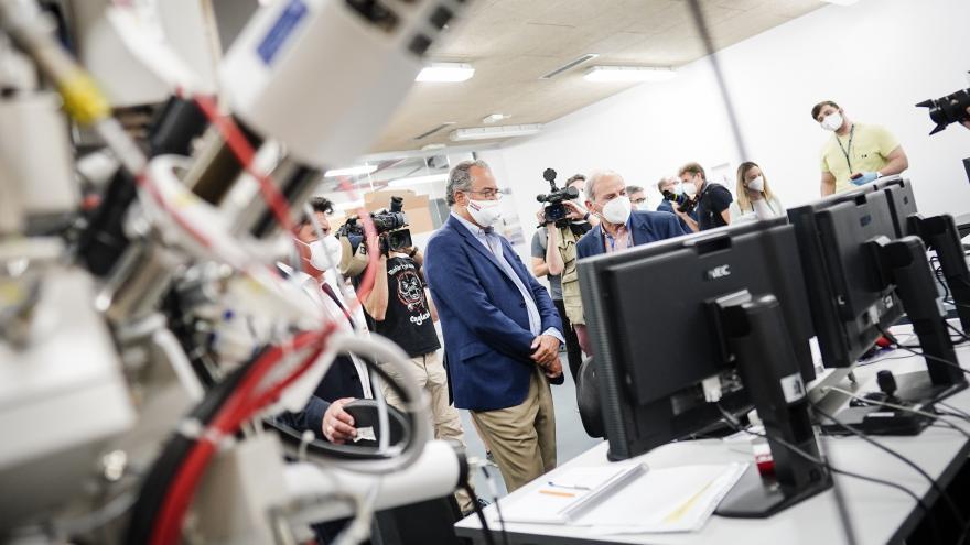 El consejero escucha las explicaciones de los técnicos en una sala con material electrónico