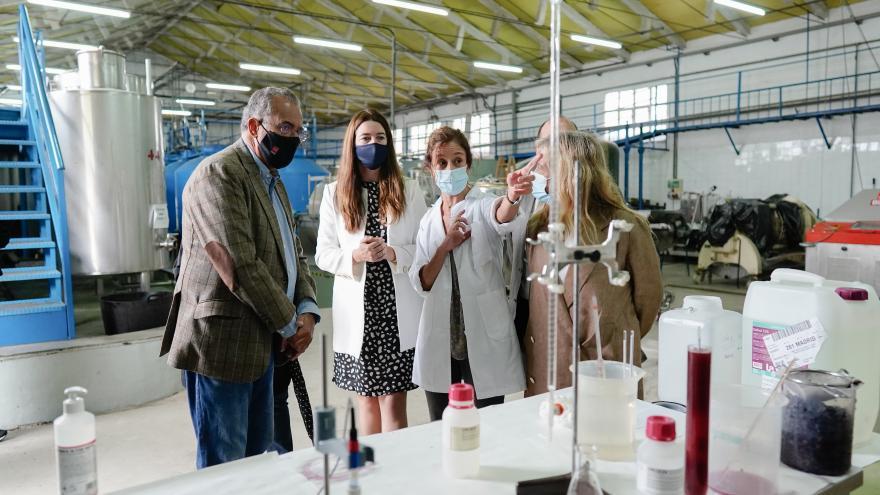 El consejero mirando unos artilugios de laboratorio y atendiendo a la explicación de las profesoras del centro