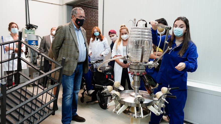 El consejero mirando una de las máquinas productoras de vino mientras atiende a la explicación de los alumnos sobre la misma