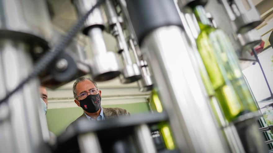 Primer plano del consejero mirando una de las máquinas productoras de vino