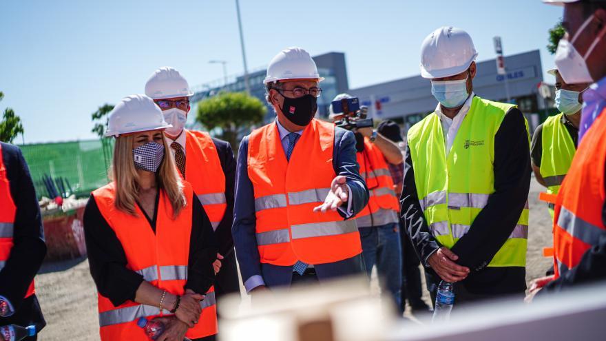 Fotografía de medio cuerpo del consejero explicando el proyecto junto al resto de miembros asistentes con chaleco reflectante y casco