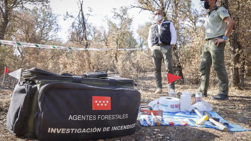 Primer plano de una mochila donde pone agentes forestales brigadas de investigación y de fondo se ve al consejero y al agente forestal