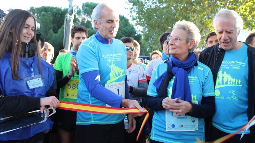El consejero de Sanidad, Enrique Ruiz Escudero, ayuda a cortar la cinta en el inicio de la carrera