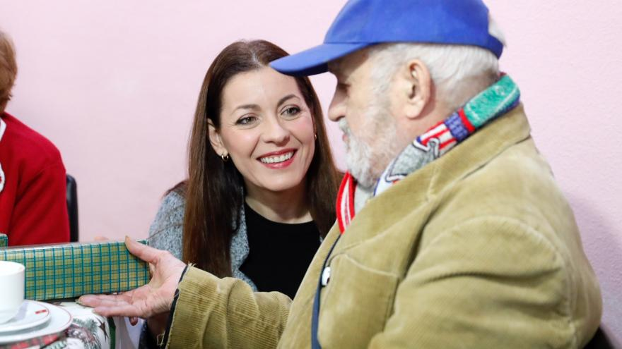 Lola Moreno entrega un presenta a uno de los ancianos de la residencia