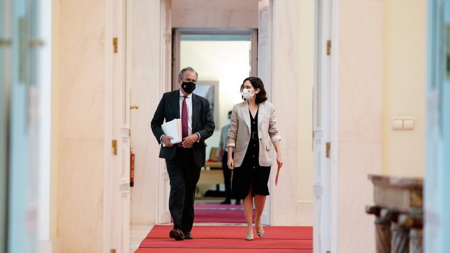 Isabel Díaz Ayuso y Enrique Ossorio caminando por un pasillo