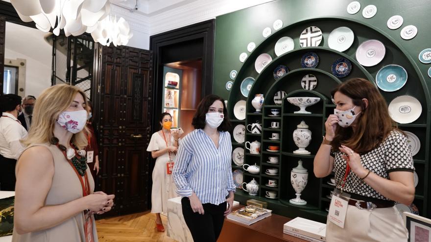 Isabel Díaz Ayuso delante una estantería verde con vajilla de porcelana blanca