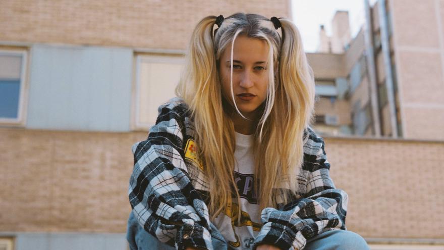 Fotografía de la artista que aparece sentada en unos escalones en al calle