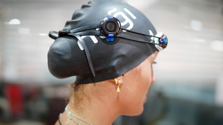 Primer plano de una nadadora con gorro de piscina y un aparato tecnológico en el mismo