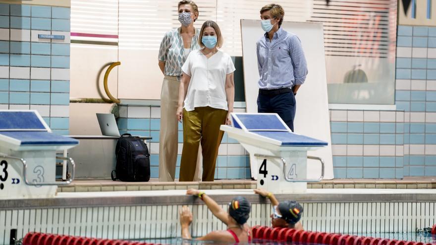La consejera con el viceconsejero y la directora general de deporte en la parte de los trampolines de la piscina mirando a dos nadadoras