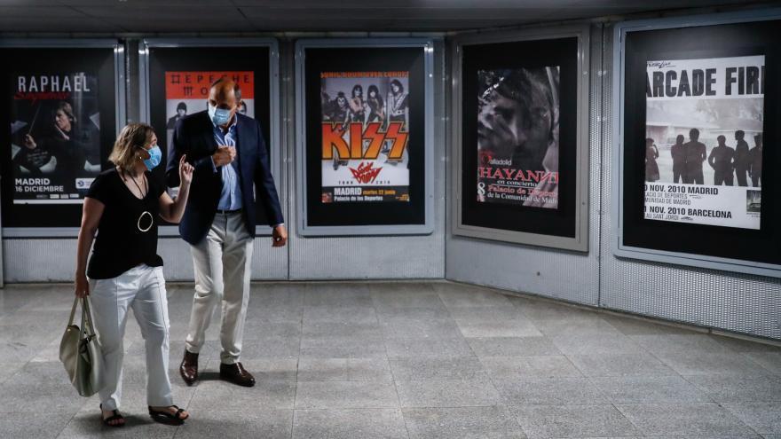 La consejera camina con el responsable por una galería de carteles antiguos de conciertos celebramos en el WiZink Center