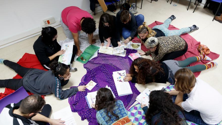 Grupo de jóvenes en el suelo consultando libros