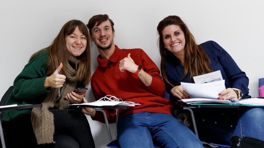 Tres jóvenes sentados sonriendo