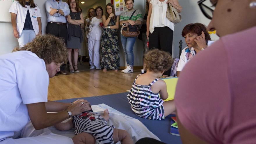 Una matrona enseña ejercicios a una madre con su bebé